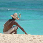 Photo straight from camera showing Dominican vendor relaxing on the beach and gazing out to sea